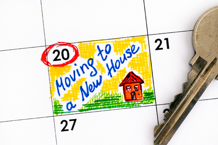 Reminder Moving to a New House in calendar with key. Closeup. Imagens