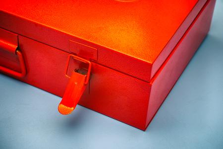 Orange metal box with lock on blue background. Close-up.
