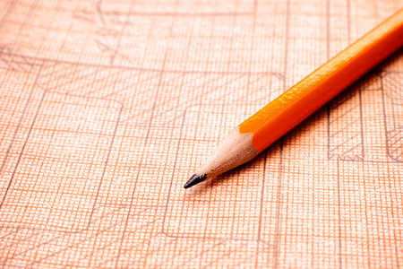 Old technical drawing on graph paper with orange pencil. Close-up.