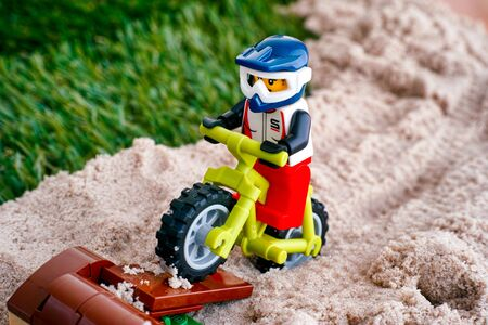 Tambov, Russian Federation - October 11, 2018 Lego cyclist minifigure on mountain bike do some jumps off the log ramp.  Close-up.