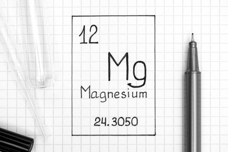 The Periodic table of elements. Handwriting chemical element Magnesium Mg with black pen, test tube and pipette. Close-up.