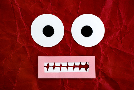 Scared emotional face made from paper. Red background.