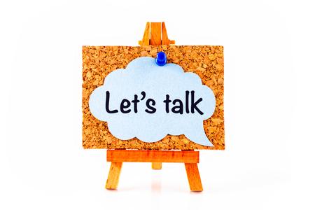 Blue speech bubble with phrase Let`s Talk on corkboard on wooden easel. White background Reklamní fotografie