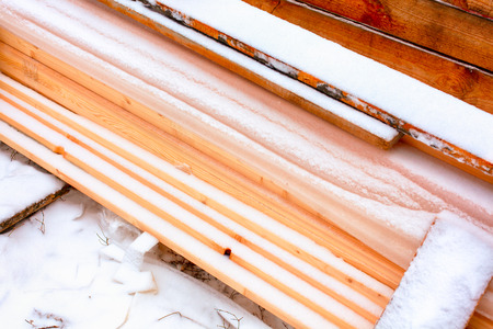 Stack of lumber covered in snow.