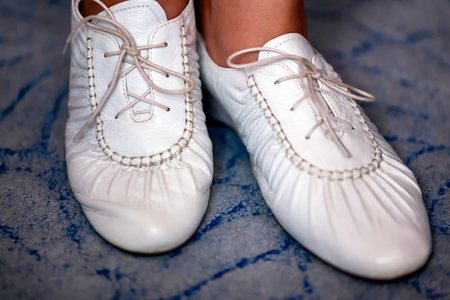 White woman shoes on feet. Blue background. Close-up.
