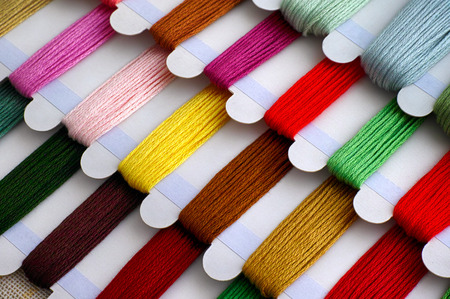 Colored embroidery threads on spools ready for cross stitch. Close-up. Archivio Fotografico - 118701482