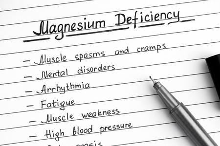 Symptoms of Magnesium Deficiency writing on list with black pen. Close-up. Archivio Fotografico