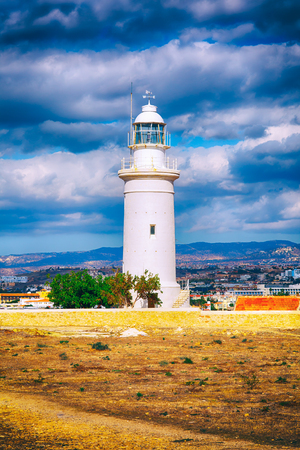 White lighthouse in Paphos Archaeological Park Cyprus with cloudy sky.