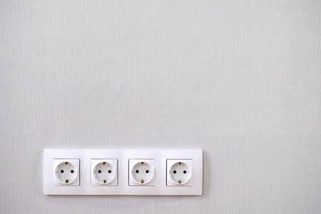 Four power sockets on gray wall. Close-up.