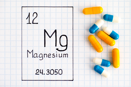 Handwriting chemical element Magnesium Mg with pills. Close-up.