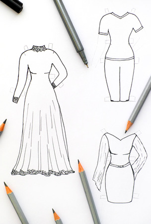 Hand drawing clothes for paper doll with black pen and pencils.