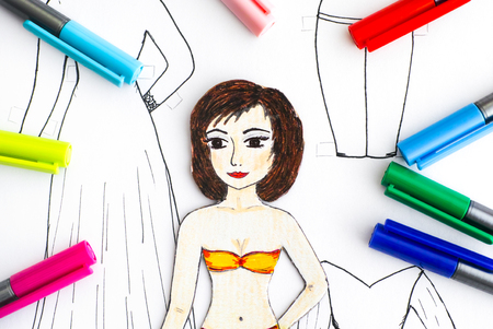 Paper doll against paper with drawing clothes and colored pens. Close-up.