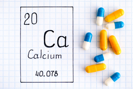 Handwriting chemical element Calcium Ca with pills. Close-up.
