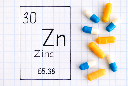 Handwriting chemical element Zinc Zn with pills. Close-up.