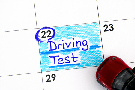Reminder Driving Test in calendar with red toy car. Close-up.