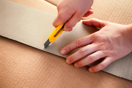 Papiermesser in den Händen, die Pappe schneiden. Nahansicht.