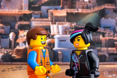 Tambov, Russian Federation - February 24, 2019 Lego Hard Hat Emmet and Lucy minifigures looking at each other and laugh against Apocalypseburg background. The Lego Movie 2. Editorial
