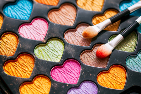 Eyeshadow heart shaped palette with two applicators. Close-up.