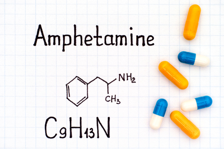 Chemical formula of Amphetamine with some pills. Close-up.