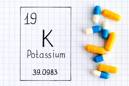 Handwriting chemical element Potassium K with pills. Close-up. Фото со стока