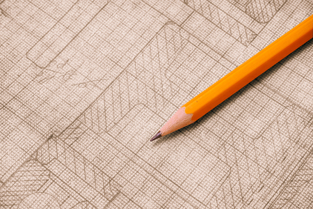 Yellow pencil with old technical drawing on graph paper. Close up.