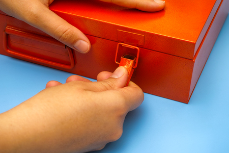 Woman hands opening lock on orange metal box on blue table. Close-up. Imagens