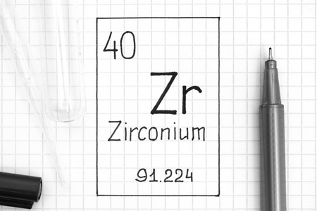 The Periodic table of elements. Handwriting chemical element Zirconium Zr with black pen, test tube and pipette. Close-up.