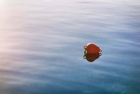 Red buoy on the sea surface. Close up. 版權商用圖片