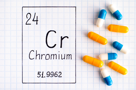 Handwriting chemical element Chromium Cr with some pills. Close-up.