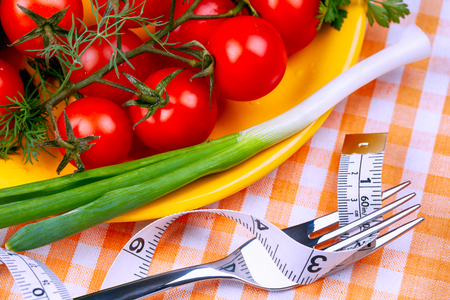 Yellow plate with cherry tomatoes and green onion and fork with tape measure on checkered tablecloth. Close-up.