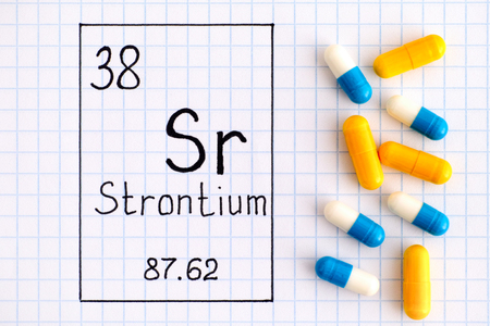 Handwriting chemical element Strontium Sr with some pills. Close-up.