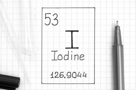 The Periodic table of elements. Handwriting chemical element Iodine I with black pen, test tube and pipette. Close-up.