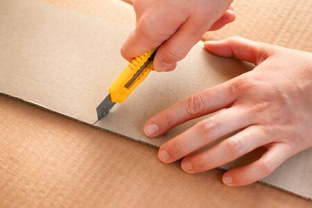 Gelbes Papiermesser in den Frauenhänden, die Stück Pappe schneiden. Nahaufnahme.