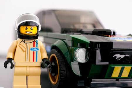 Tambov, Russian Federation - July 02, 2019 Lego 1968 Ford Mustang Fastback driver minifigure by LEGO Speed Champions near his car. Studio shot.