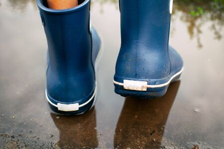 Man in blue rubber boots walking through the puddle. Back view.