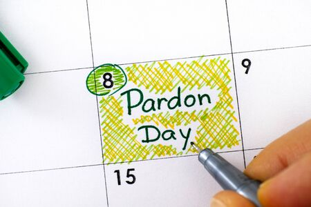 Woman fingers with pen writing reminder Pardon Day in calendar. September 8. Close-up.