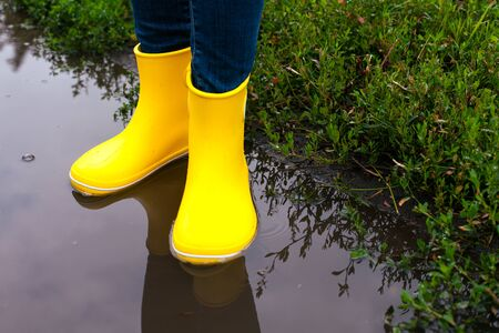 Woman in yellow rubber boots standing in the puddle outdoors.