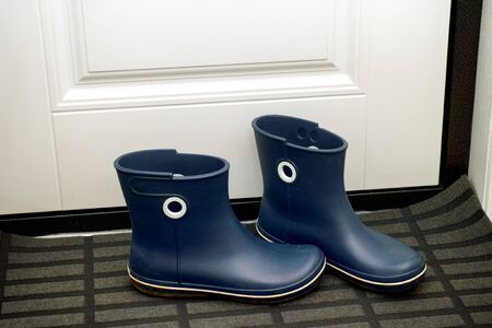 Pairs of blue rubber boots standing in hallway near door. Close-up. 版權商用圖片