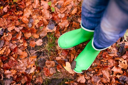 Child in green rubber boots standing on fallen leaves outdoors.