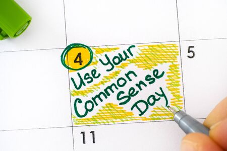 Woman fingers with green pen writing reminder Use Your Common Sense Day in calendar. November 4. Close-up.