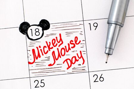 Reminder Mickey Mouse Day in calendar with pen. November 18. Close-up.