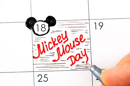 Woman fingers with pen writing reminder Mickey Mouse Day in calendar. November 18.