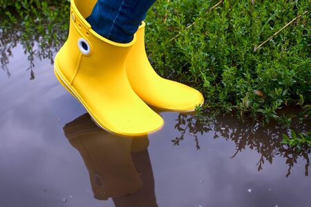 Woman in yellow rubber boots standing in the puddle. Close-up.