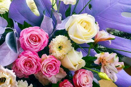 Hermosa composición floral con rosas, crisantemos y hojas de violeta. De cerca.