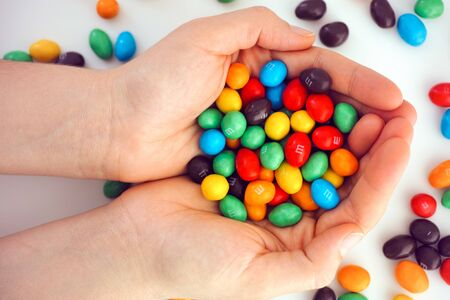 Tambov, Russian Federation - December 05, 2019 M&Ms candy in woman hands. White background.