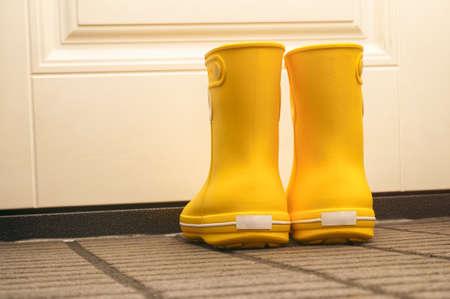 Pair of yellow rubber boots standing in hallway near door. Close-up.