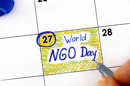 Woman fingers with pen writing reminder World NGO Day in calendar. February 27. 免版税图像