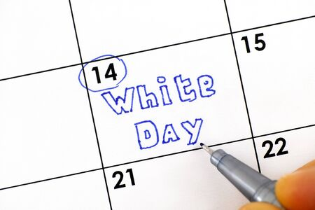 Woman fingers with pen writing reminder White Day in calendar. March 14.