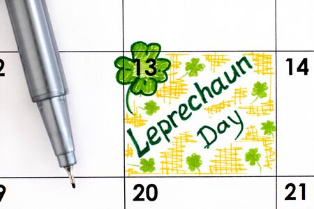 Reminder Leprechaun Day in calendar with pen. May 13.