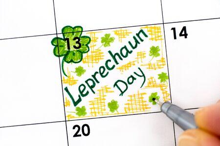 Woman fingers with pen writing reminder Leprechaun Day in calendar. May 13.  Zdjęcie Seryjne